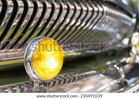 Round yellow head light of retro automobile. In background, shiny chrome radiator grille of vehicle, with reflection. Background slightly blurred. - stock photo