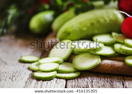 Round zucchini slices and fresh radish, vintage wooden background, selective focus, shallow depth of field - stock photo