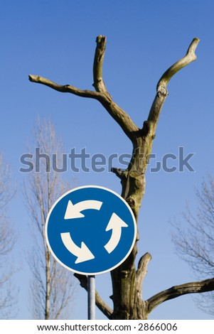 Roundabout sign in front of dead tree. Could be used in recycling issue.