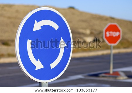 roundabout signal and halt sign in a road
