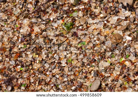 Rounded glass shards or seaglass on gravel beach abstract background texture pattern