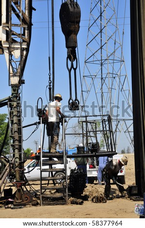 Roustabouts doing dirty and dangerous work on an oil well servicing rig - stock photo