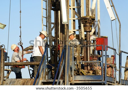 Roustabouts work on lower platform of oil drilling rig, Kern County, California