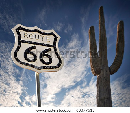 Route 66 road sign with Saguaro Cactus and wild dramatic sky - stock photo
