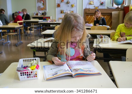 Rovaniemi, Finland - May, 2007: Young girl counts numbers with help of her hands during the lesson of mathematics at primary school in Finland. Documentary editorial - stock photo
