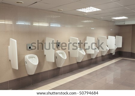 Row automatic urinals in a modern toilet - stock photo