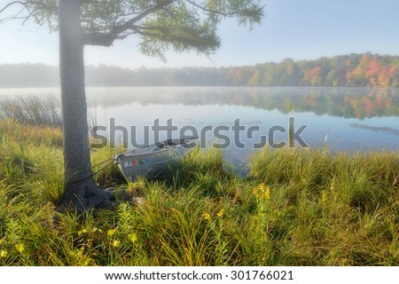 Row boat chained to a tree on a foggy Autumn morning at Marl Lake, Michigan - stock photo