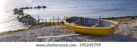 Row boat laying on a stone beach next to the water.GN - stock photo