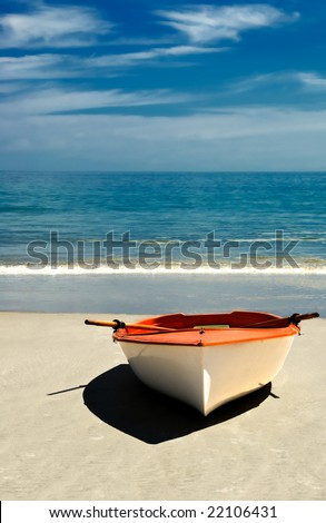 Row boat on the beach of an island paradise ready for a journey. - stock photo