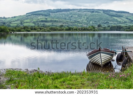 Row boat tied up at a dock on an Irish lake - stock photo
