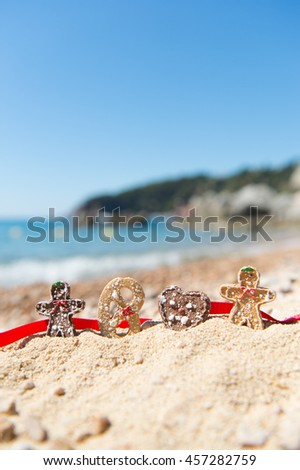 Row Christmas cookies at the summer beach - stock photo