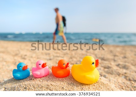Row colorful ducks at the summer beach - stock photo