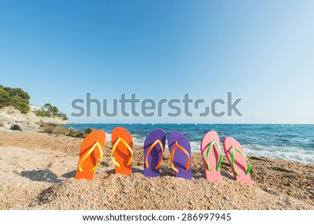 row colorful flip flops at the beach - stock photo