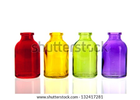 Row colorful glass bottles in red, yellow, green and purple - stock photo