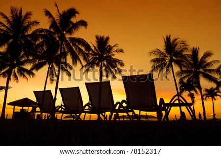 Row deckchairs on beach at sunset, Tanjung Aru, Malaysia. - stock photo
