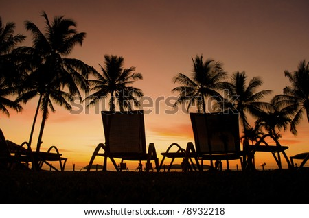 Row deckchairs on beach at sunset, Tanjung Aru, Malaysia - stock photo