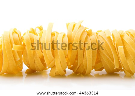 row dry nest pasta on white with reflection isolated over white - stock photo
