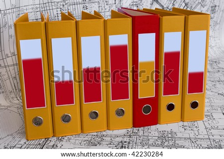 Row from the yellow file folders and one red folder with clean blanks for your text. Black and white project drawings are background - stock photo