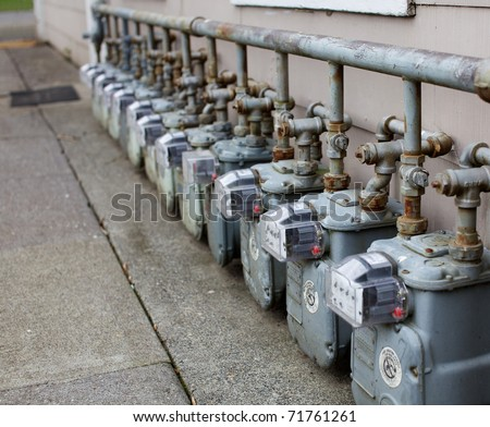 Row gray gas meters at an apartment complex - stock photo