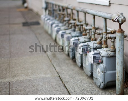Row gray gas meters at an apartment complex done with a narrow field of focus - stock photo