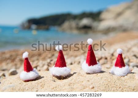 Row hats of Santa Claus at the summer beach - stock photo