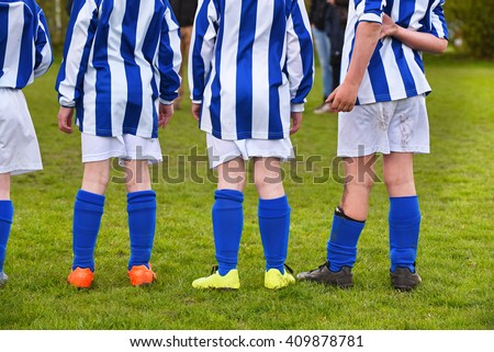 Row legs of soccer playing kids in blue white striped shirts, waiting for a penalty.