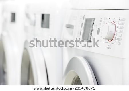 row line of modern white laundry washing machines - stock photo