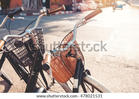 Row of a vintage bicycle for rent in the city street with sunlight of sunset (vintage color tone)