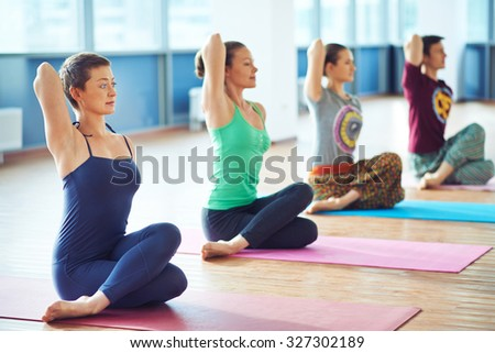 Row of active people exercising in gym - stock photo