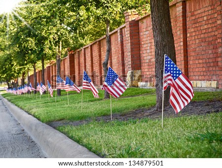 Row of American flags displayed on the street side in celebration of Independence Day, shallow depth of field - stock photo