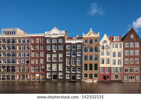 Row of ancient canal houses in the Dutch capital city Amsterdam against a blue sky - stock photo