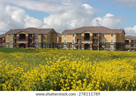 Row of apartments near spring field - stock photo