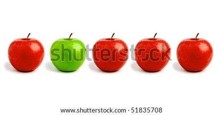Row of apples, one green standing out - stock photo