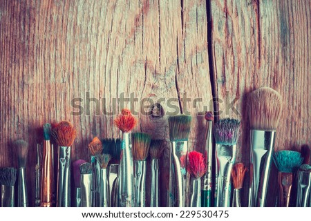 row of artist paintbrushes closeup on old wooden rustic table, retro stylized - stock photo