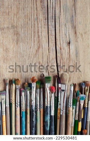 row of artist paintbrushes on old wooden rustic table - stock photo