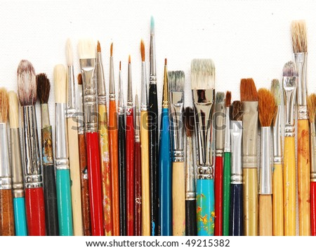 row of artists' paintbrushes against natural canvas - stock photo