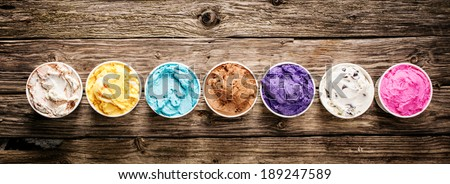 Row of assorted flavors and colors of gourmet Italian ice cream served in plastic takeaway tubs on a rustic wooden table, horizontal banner format with copyspace - stock photo