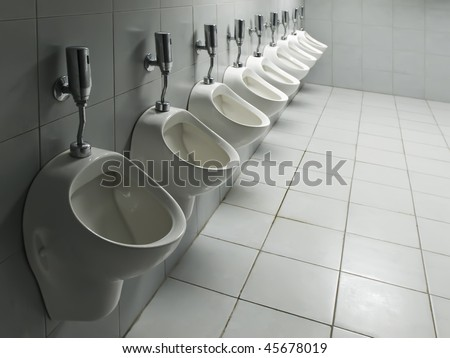 Row of auto flushing ceramic urinals in a public toilet