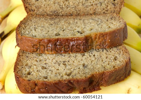 row of banana bread stacked on whole bananas closeup - stock photo