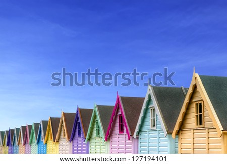 row of beach huts with a deep blue sky - stock photo