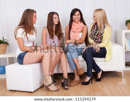 Row of beautiful stylish young ladies sitting on a couch in a living room - stock photo