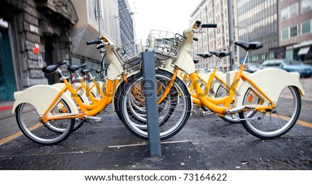 Row of bicycles for rent in Milano, Italy - stock photo