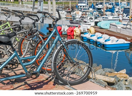Row of bikes for rent at a harbor resort. Touring bicycles parked in a row at bike stand overlooking the marina. Paddle boats and yachts in blurred background.  - stock photo