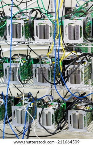 Row of bitcoin miners set up on the wired shelfs. - stock photo