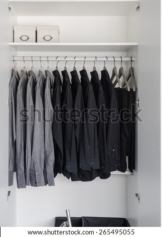 row of black and grey shirts hanging on coat hanger in white wardrobe - stock photo