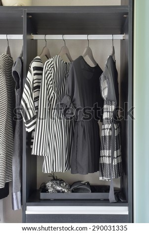 row of black and white dress in wardrobe at home - stock photo