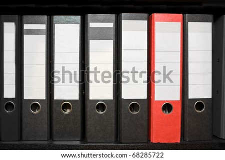 Row of black archive folders with one red folder - stock photo