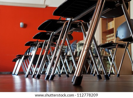 Row of black chair on red wall. - stock photo
