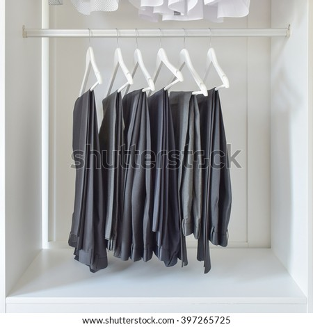 row of black pants hanging in white wooden wardrobe - stock photo