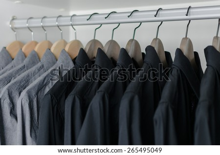 row of black shirts hanging on coat hanger in white wardrobe - stock photo